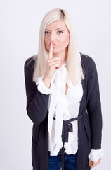 Young woman with finger on lips over white background