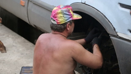 Rural Man Repairing a Car