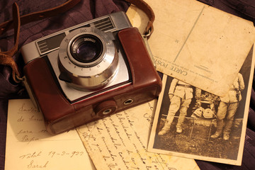 old camera with postcards and photo