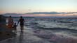 Family of three walking barefoot along the shore