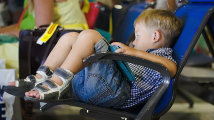 Boy amuse himself with pad in waiting room