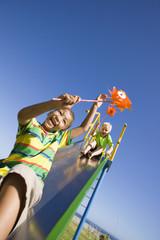 Boys holding pinwheels on slide at playground