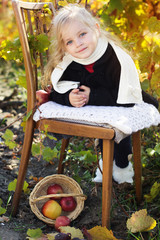 Adorable little girl with apples, autumn time