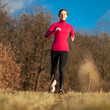 Young woman running outdoors on a lovely sunny winter/fall day