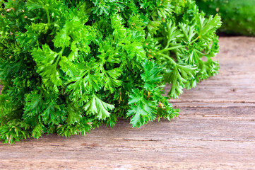 tied fresh parsley on wooden surface