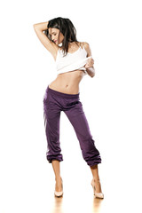 woman in sweatpants and a shirt posing on a white background