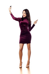 happy young woman with a tight purple dress take a selfie