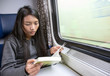 woman reading a book on the driving train