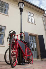 red vintage bicycle leaning against a lamp