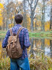 male hiker stand near autumn lake