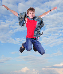 full length portrait of running jumping boy in the sky