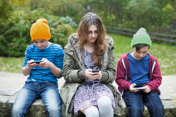 three kids with phones