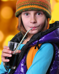 girl with hat drinking cola against yellow background