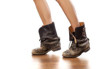 Pretty female legs in muddy military boots