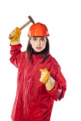 Crazy young helmeted woman worker holding a hammer