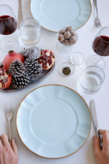 Holiday table setting, dinner party with hands holding cutlery