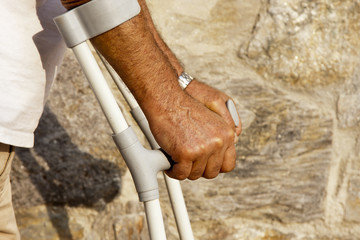 arms of older man leaning on crutches