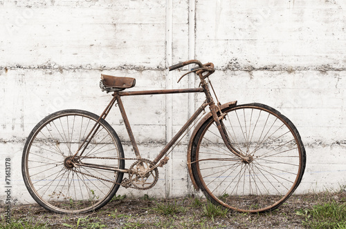 Foto op Aluminium Fiets Antique or retro oxidized bicycle outside on a concrete wall