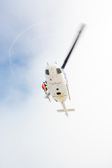 Helicopter with a rescuer standing on its ledge