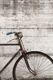 Antique or retro oxidized bicycle outside on a concrete wall - 71613513