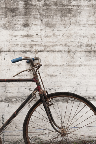 Staande foto Fiets Antique or retro oxidized bicycle outside on a concrete wall