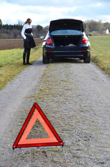 Broken car, girl and warning triangle