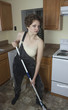 Mad woman with short hair mopping floor in kitchen