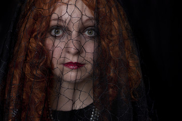 Pretty redhead wearing black dress and black veil