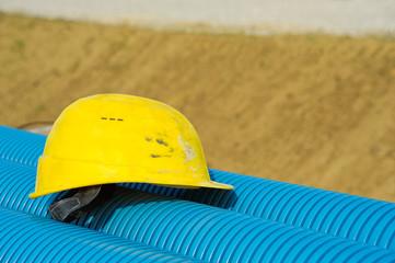 Gelber Helm liegt auf blauem Rohr