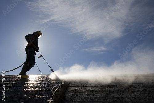 Worker on top of factory hall, with high pressure washer - 71614985
