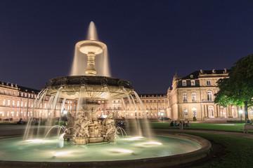 Beleuchtetes Schloss Stuttgart bei Nacht mit Brunnen