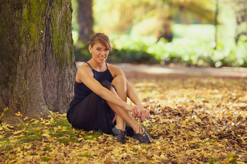 Beautiful ballerina sitting in nature tying her ballet shoes