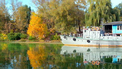 Forest lake in the autumn. Old boat is moored near the shore