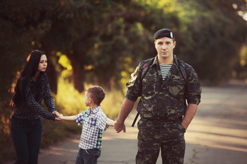 Family and soldier in a military uniform say goodbye