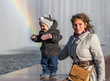 Smiling toddler with his mother standing near rainbow