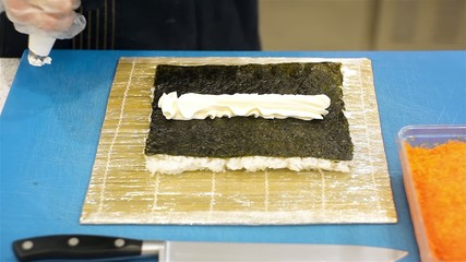 Pouring philadelphia cheese on nori with pastry bag