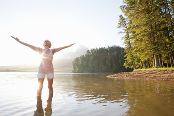 Older woman standing with arms outstretched in lake