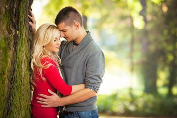 Young couple embracing on a sunny autumn day in nature