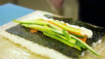 Adding cucumber during making sushi roll