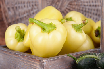 Yellow peppers in crate with cucumbers on wicker background