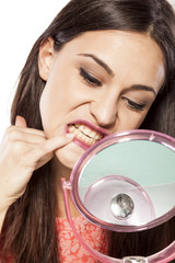 young beautiful woman clean her teeth with her ​​fingers