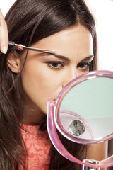 young beautiful woman cuts her eyebrows with scissors