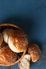 Tasty buns with sesame in wicker basket,