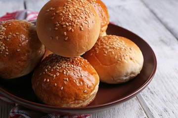 Tasty buns with sesame on plate, on color wooden background