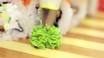 Adding wasabi on plate with sushi