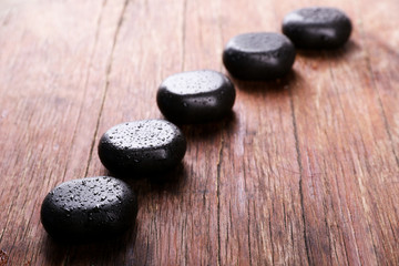 Spa stones with drops on wooden background