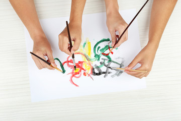 Two girls painting with paintbrush and colorful paints