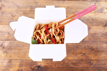 Fried noodles and sticks in takeaway box on wooden background