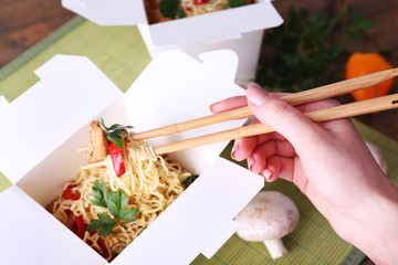 Chinese noodles and sticks in takeaway box on mat background