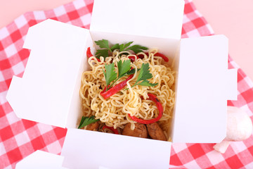 Chinese noodles in takeaway boxes on fabric background